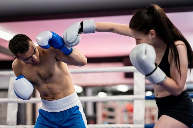男性と女性のボクサーが一緒にトレーニング