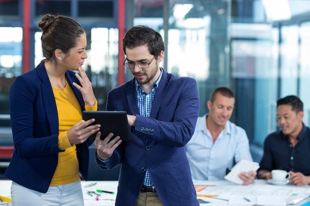 Мужской и женский руководитель бизнеса обсуждая над цифровой таблеткой