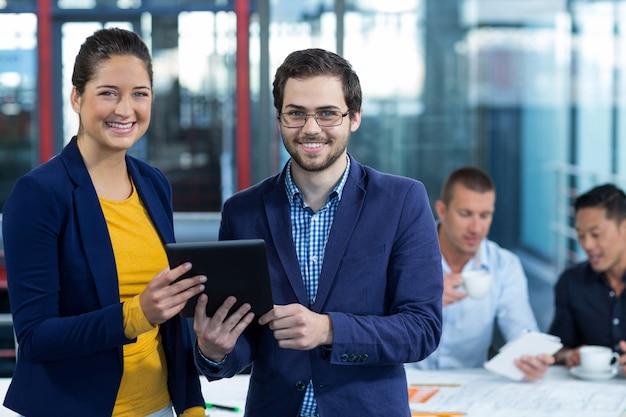 Мужской и женский руководитель бизнеса держа цифровую таблетку