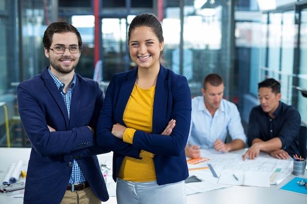 Мужской и женский руководитель бизнеса, улыбаясь в то время как коллега взаимодействует над планом