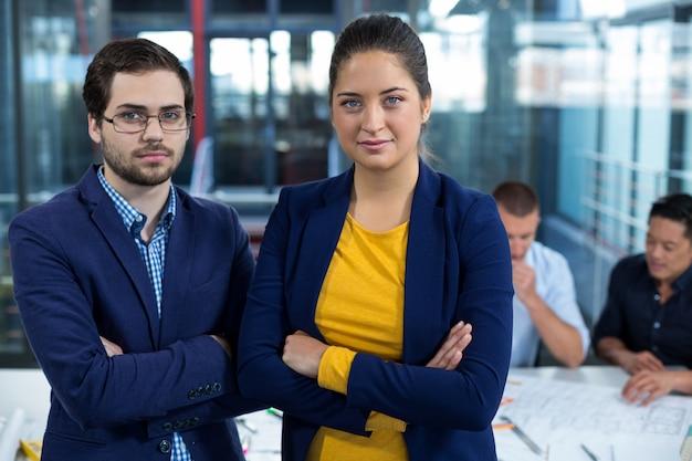 Мужской и женский руководитель бизнеса, стоя со скрещенными руками