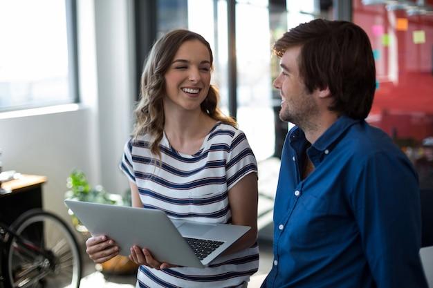 ラップトップを使用しながら対話する男性と女性の経営幹部