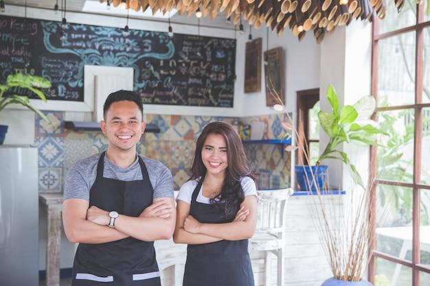 Владельцы кафе мужского и женского пола, стоящие со скрещенными руками в кафе