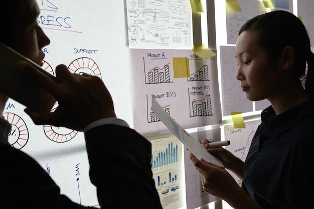 ビジネスグラフと図でガラスの壁のそばに立っている男性と女性の同僚