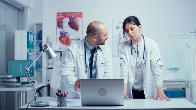 男性と女性の医師が患者に関する医学的問題について互いに相談し合っています。本物の現代の私立病院クリニックルームヘルスケアシステムの医学と治療