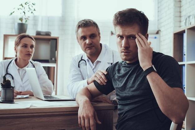 사무실에서 테이블에서 남성과 여성의 의사입니다. 선수의 머리가 아프다.