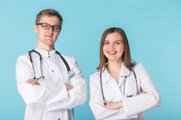 파란색 배경에 흰색 가운을 입은 남성과 여성 의사