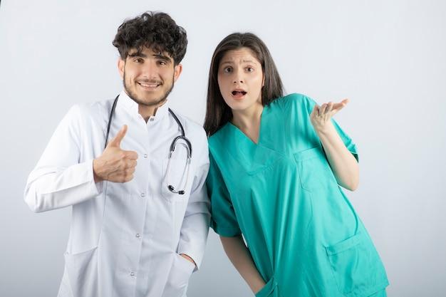 카메라를 보고 엄지손가락을 보여주는 남성과 여성 의사.