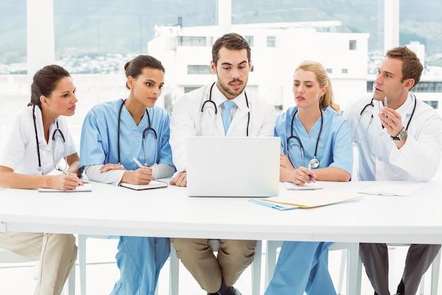 Мужчины и женщины-врачи, используя ноутбук