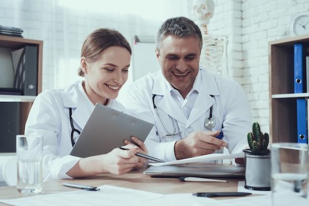 Мужские и женские врачи со стетоскопами на столе в офисе. врачи сравнивают записи.