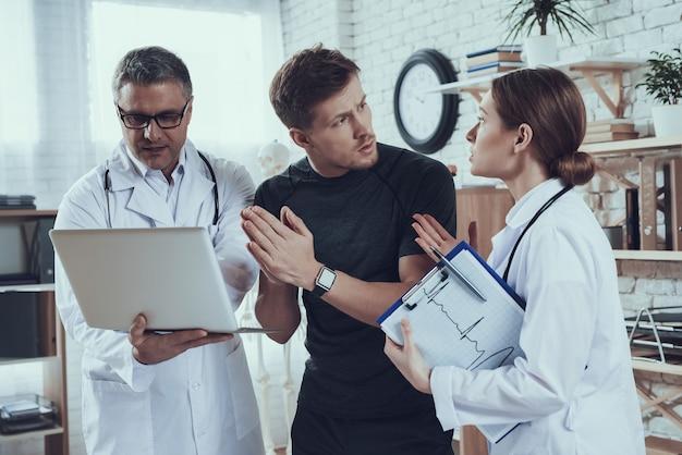 청진 기 사무실에서 남성과 여성의 의사입니다. 의사는 노트북에 스포츠맨에게 보여주고 있습니다.