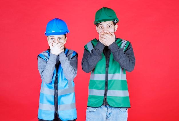 ヘルメットとギアを身に着けている男性と女性のエンジニアは怖くて怖がっているように見えます。