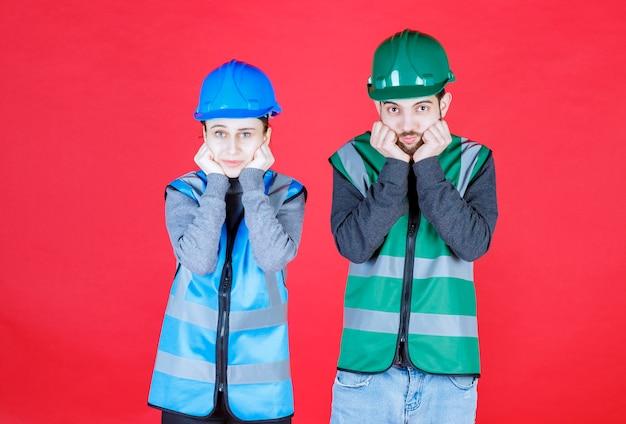 ヘルメットとギアを身に着けている男性と女性のエンジニアは、混乱して思慮深く見えます。