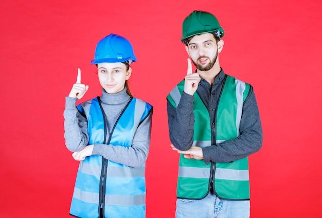 ヘルメットとギアを身に着けている男性と女性のエンジニアが現れます。