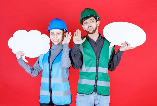 헬멧을 들고 구름과 ovale 모양 정보 보드를 들고 뭔가를 멈추려 고하는 남성과 여성 엔지니어.