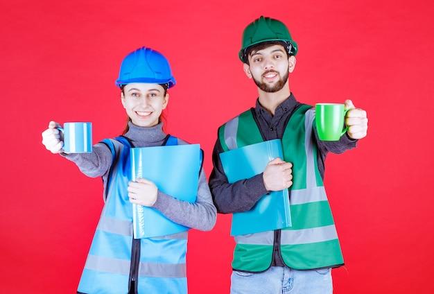 青と緑のマグカップを保持し、フォルダーを報告し、歓声を上げるヘルメットを持つ男性と女性のエンジニア。