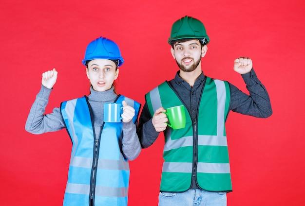 헬멧 파란색과 녹색 머그잔을 들고 만족 기호를 보여주는 남성과 여성 엔지니어.
