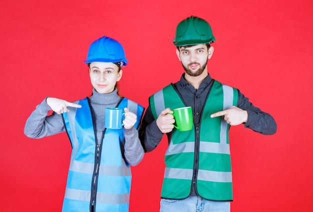 파란색과 녹색 머그잔을 들고 헬멧 남성과 여성 엔지니어.