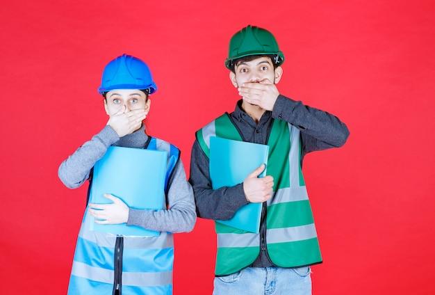 Инженеры мужского и женского пола в шлеме держат папки с отчетами и выглядят напуганными и напуганными.