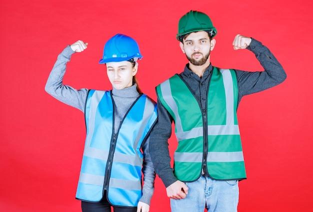 パワフルで前向きなヘルメットをかぶった男性と女性のエンジニア。