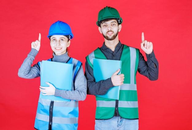 青いフォルダーを保持し、周りの誰かを指しているヘルメットを持つ男性と女性のエンジニア。