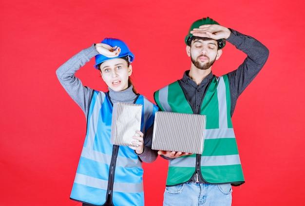 銀のギフトボックスを保持し、疲れているように見えるヘルメットを持つ男性と女性のエンジニア。
