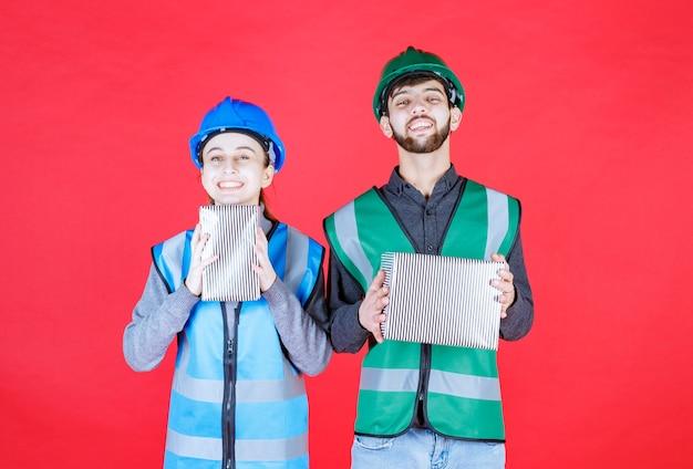 銀のギフトボックスを保持しているヘルメットを持つ男性と女性のエンジニア。 無料写真