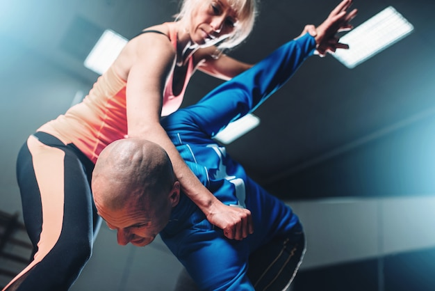Бойцы мужского и женского пола, техника самообороны, тренировка самообороны с личным инструктором в тренажерном зале, боевые искусства
