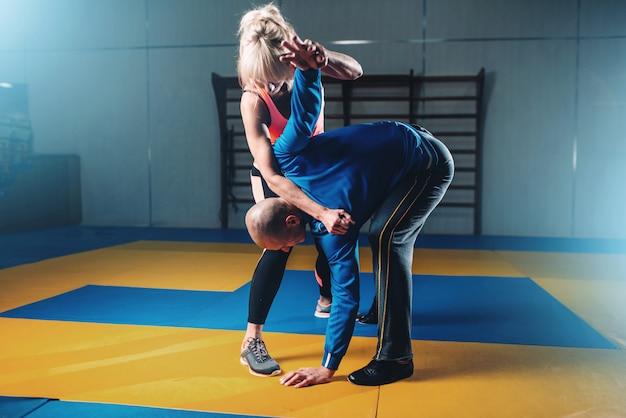 Бойцы мужского и женского пола, техника самообороны, тренировка самообороны с личным тренером в тренажерном зале, боевые искусства