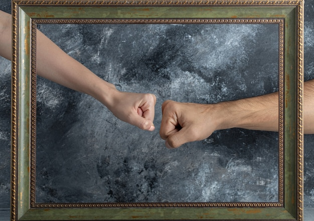 男性と女性の拳は額縁の真ん中で出会う。