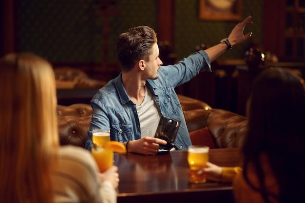 Друзья мужского и женского пола пьют алкоголь за столиком в баре. группа людей отдыхает в пабе, ночной образ жизни, дружба, празднование события