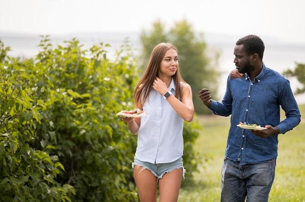屋外でバーベキューを楽しんでいる男性と女性の友人