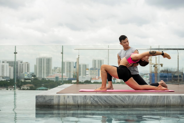 Друзья-мужчины и женщины, практикующие йогу у бассейна