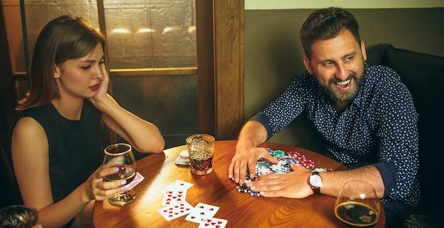 木製のテーブルに座っている男性と女性の友人。