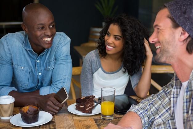 Друзья мужского и женского пола разговаривают за столом в кофейне