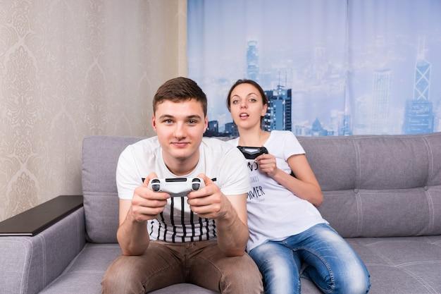 편안한 분위기에서 집에서 함께 소파에 앉아 비디오 게임을 하는 남성과 여성 게이머