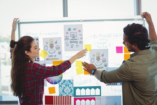 付箋紙について議論する男性と女性のグラフィックデザイナー