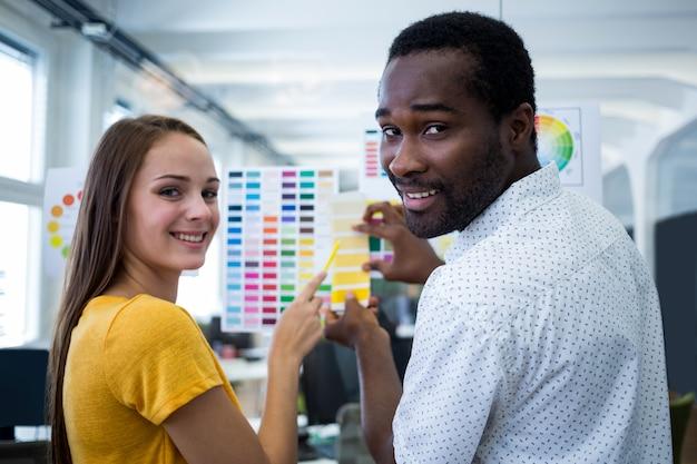 Мужские и женские графические дизайнеры взаимодействующими над цветовой шкалой