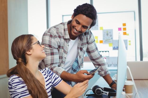 책상에서 서로 상호 작용하는 남성 및 여성 그래픽 디자이너