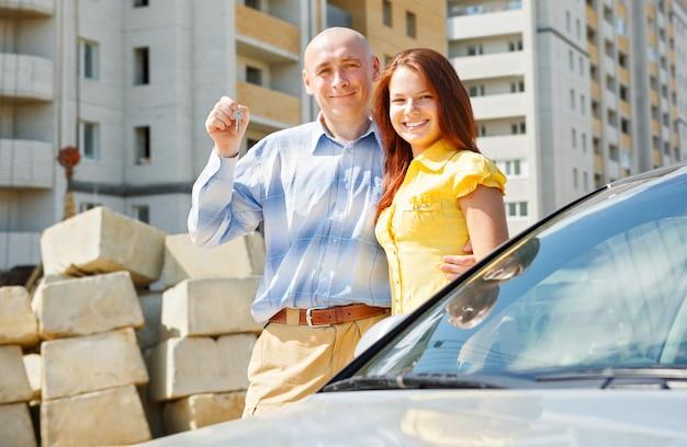 Мужская и женская рука счастливые ключи от дома зеленый на открытом воздухе здание