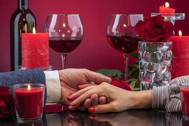 Мужские и женские руки отображаются на зеркальной поверхности среди тающих свечей.