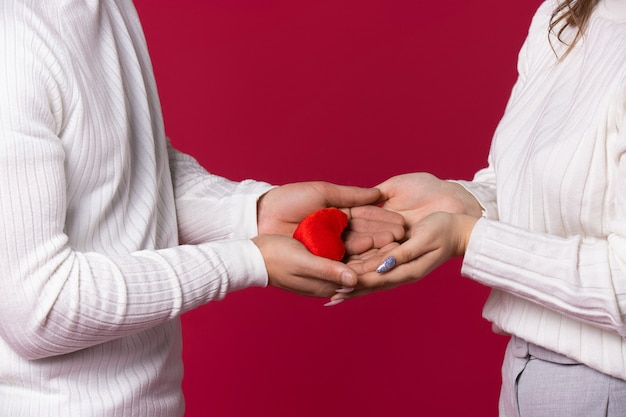 남성과 여성의 손은 사랑의 상징을 들고 있습니다. 빨간색 배경에 봉 제 붉은 마음.