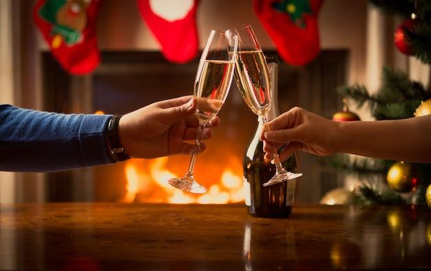 クリスマスに飾られたリビングルームでシャンパンのグラスでチリンと鳴る男性と女性の手
