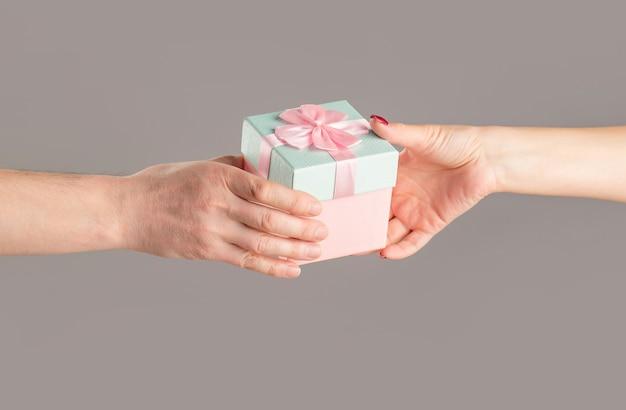 ピンクのギフトボックスを保持している男性と女性の手。女の子は男に贈り物をします。贈り物を持っている女性の手。手にギフトボックス、サプライズと休日のコンセプト。バレンタインデーの贈り物を持っている男の手。