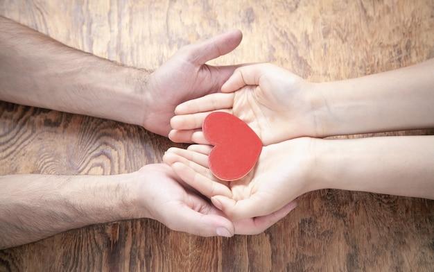 붉은 마음을 잡고 남성과 여성의 손입니다.
