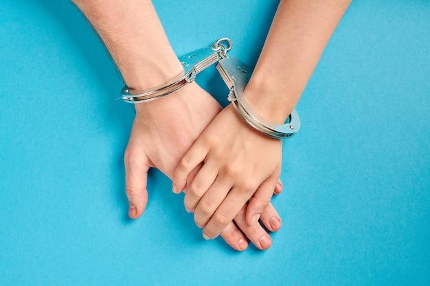 手錠をかけた男性と女性の手。永遠の愛。婚前契約、愛のカップルの義務。