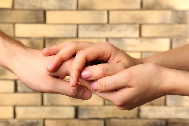 壁の背景に男性と女性の手