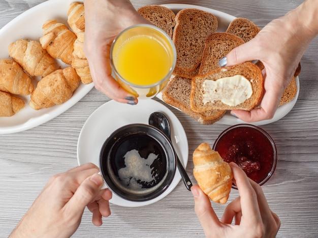 블랙 커피 한 잔과 오렌지 주스 한 잔을 든 남성과 여성의 손. 크루아상, 빵, 배경에 잼이 있는 유리 그릇. 평면도. 아침 식사를 위한 음식과 음료