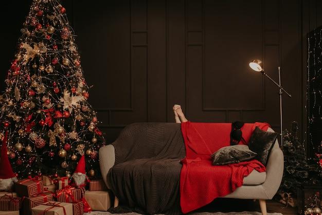 Мужчина и женщина, держась за руки, переплетенные голыми руками, спрятались за диванчиком. украшенный дом на новый год.