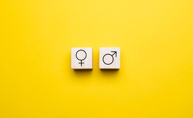 黄色の背景の木製ブロックに男性と女性のアイコンシンボル。フラットレイビュー。